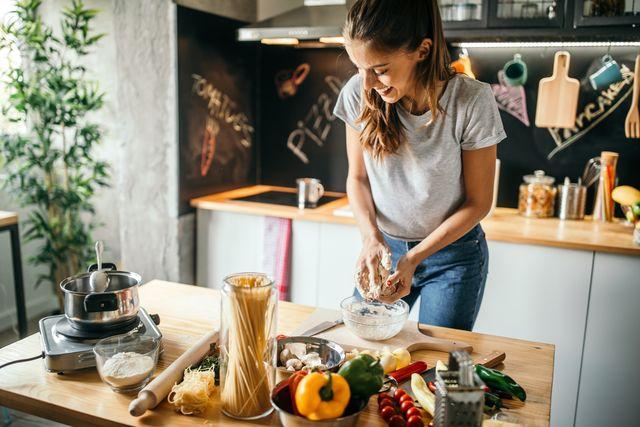 donna in cucina impasta, sul tavolo verdure