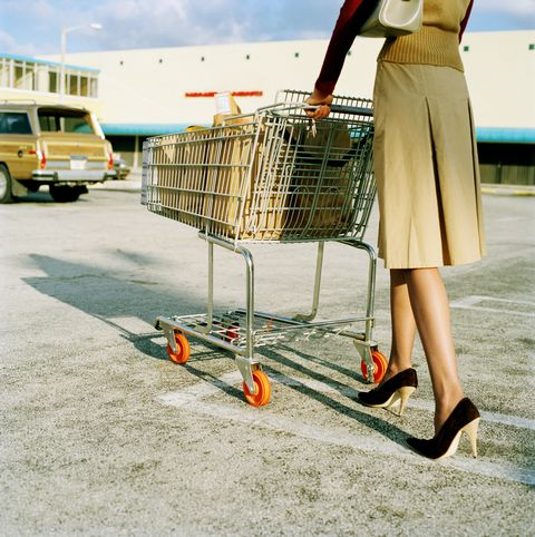 Young woman pushing trolley full of groceries in car park, low section