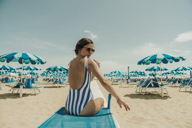 mujer poniéndose crema solar en la playa