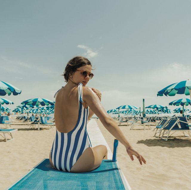 young woman putting sunscreeen at italian beach