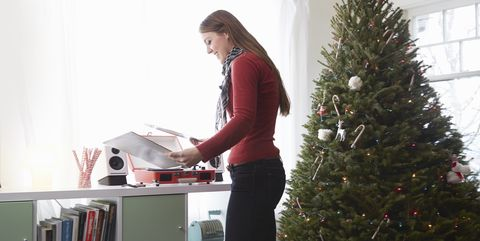 young woman putting vinyl on record player at christmas - Best Christmas Albums Of All Time