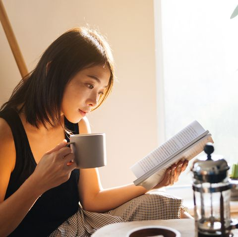 young woman reading book while drinking coffee