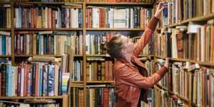 Young woman reading in second hand bookstore
