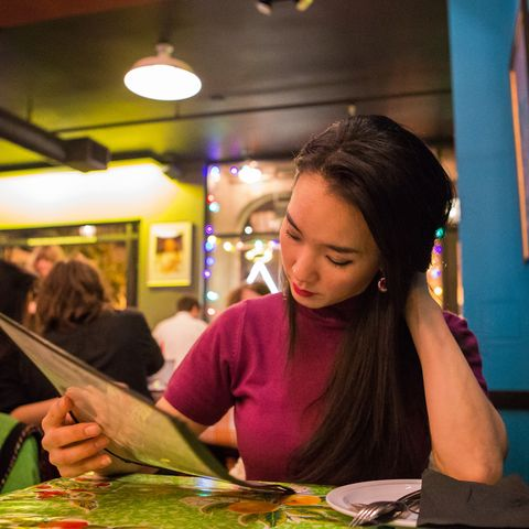 healthy dining out - Young Woman Reading Menu At Restaurant
