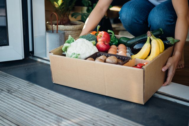 young woman receiving fresh food home delivery