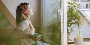 Young woman relaxing at home with a cup of tea, listening music
