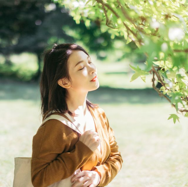 young woman relaxing in nature with eye closed