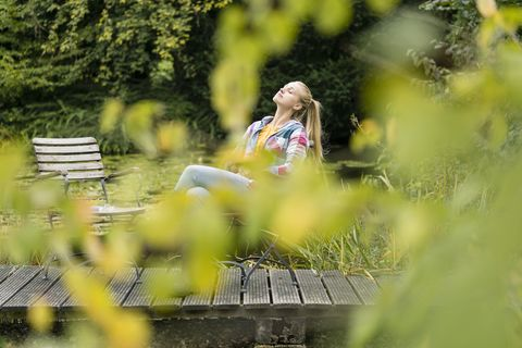 Young woman relaxing on jetty in garden