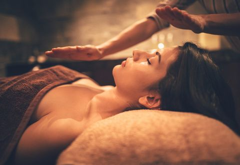 Young woman relaxing with body and face massage at spa