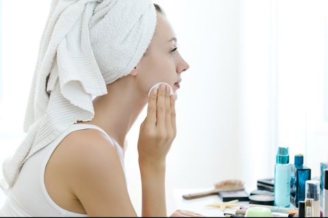Young woman removing makeup from her face