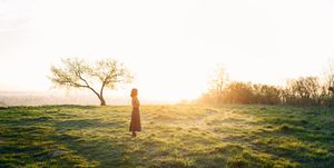Young woman resting in the field at sunset