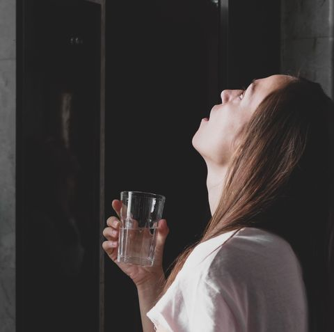young woman rinses her mouth with water and looking at mirror