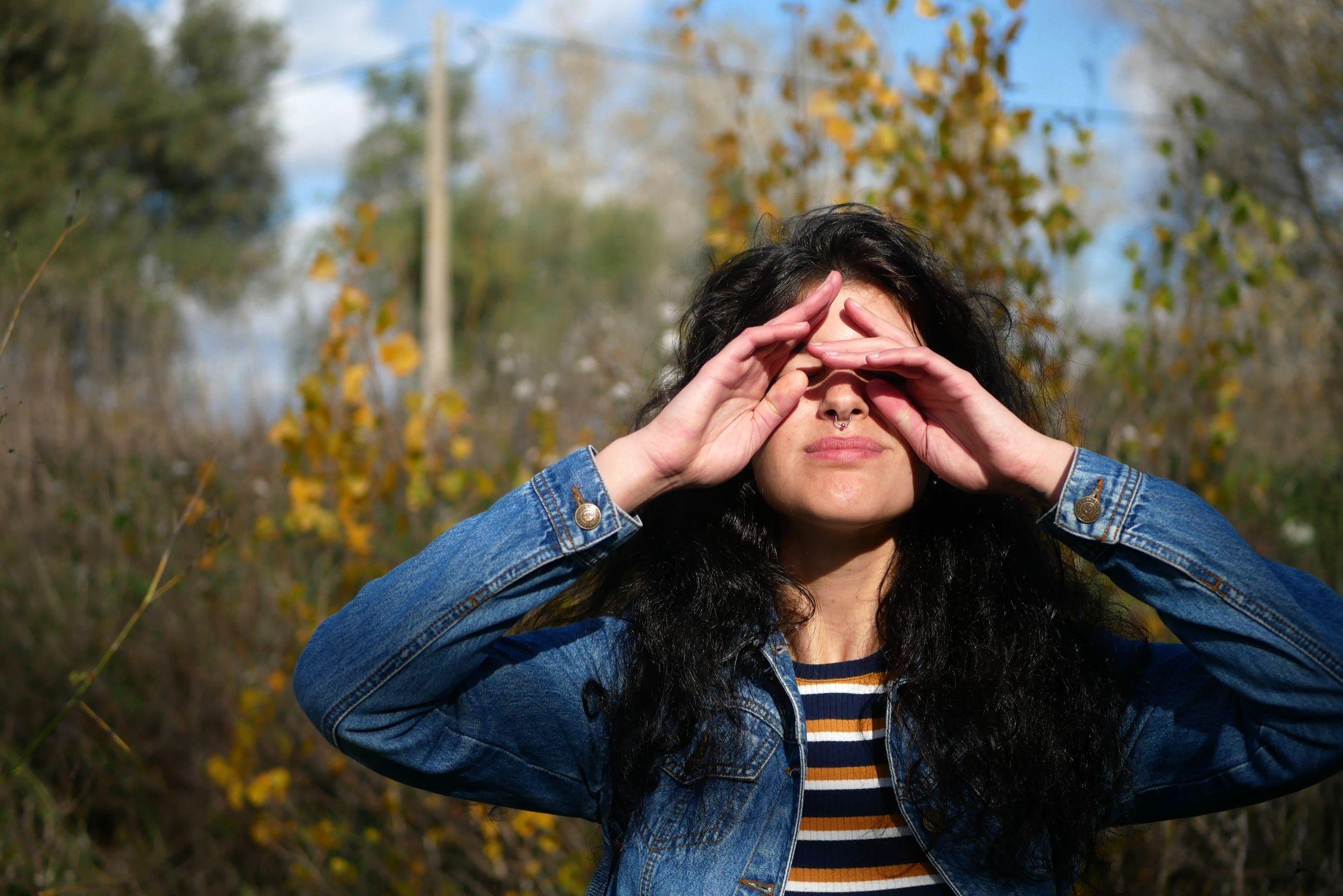 jovem esfregando os olhos em pé contra árvores na floresta