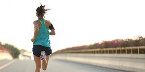 young woman runner running on city bridge road