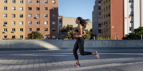 Young woman running along apartment blocks in the city