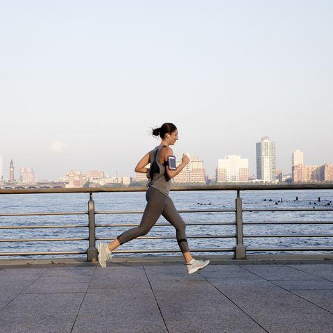 Young woman running along Hudson River
