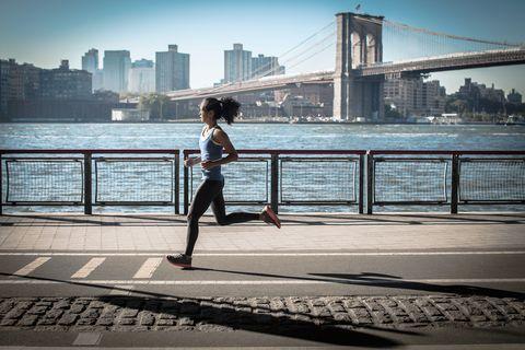 Young woman running along waterfront, New York, USA