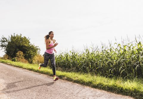 Young woman running on country lane
