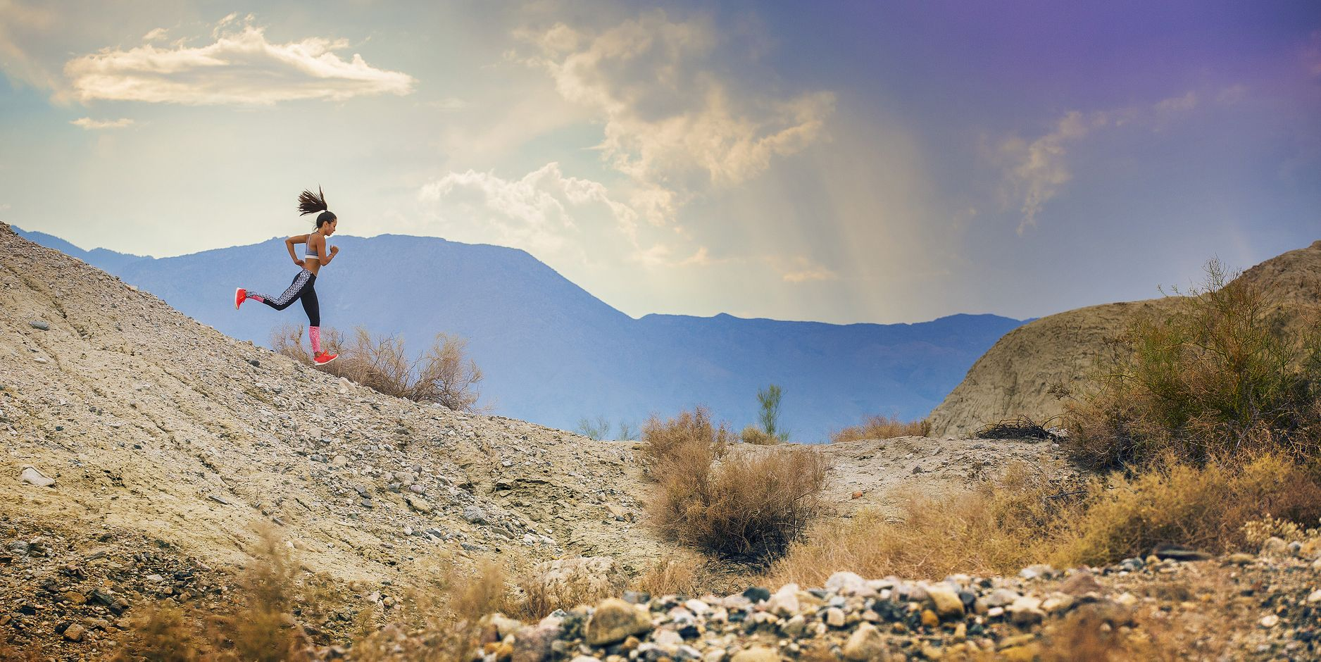 Young woman running on mountain at sunset