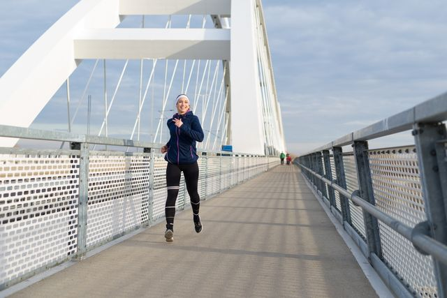 Young woman running on the bridge