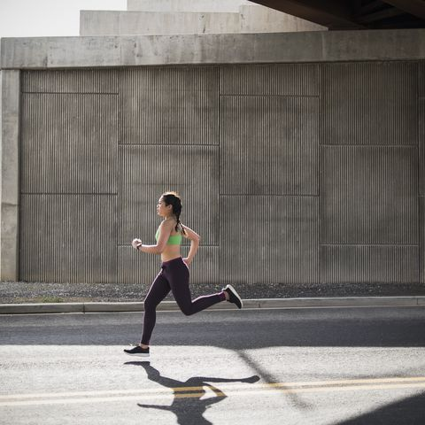 young woman running under freeway overpass