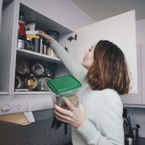 young woman searching in kitchen cabinet