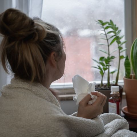 a young woman sick at home stares out the window on a rainy day