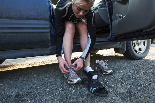 a young woman sits on the seat of her car with the door open changing shoes before going for a run