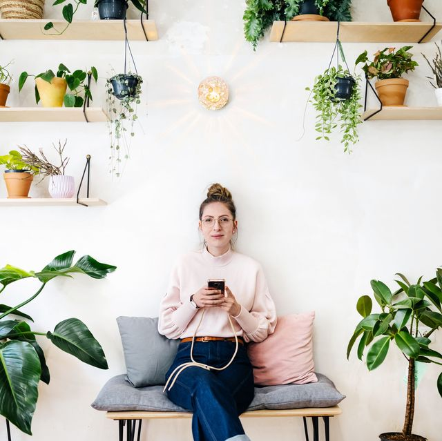 young woman sitting amongst plants in quirky café