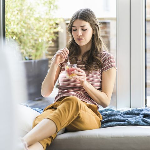 young woman sitting at the window at home having a snack