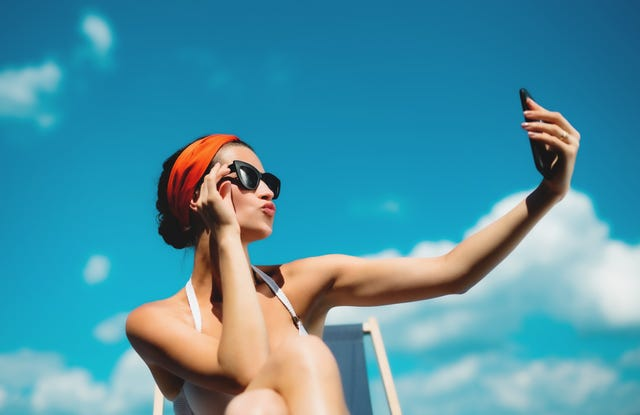 young woman sitting by swimming pool outdoors in backyard garden doing a selfie