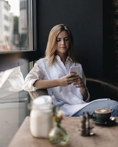 Young woman sitting in cafe using smartphone