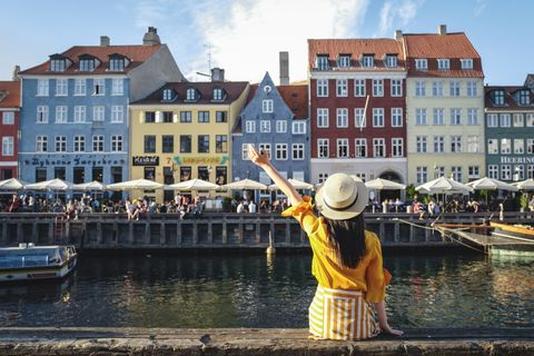 Young woman sitting in front of colorful buildings along Nyhavn (New Harbour), Copenhagen, Denmark