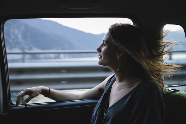 young woman sitting on backseat in a car looking out of window