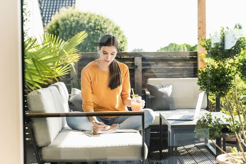 young woman sitting on couch on terrace with healthy drink and notebook