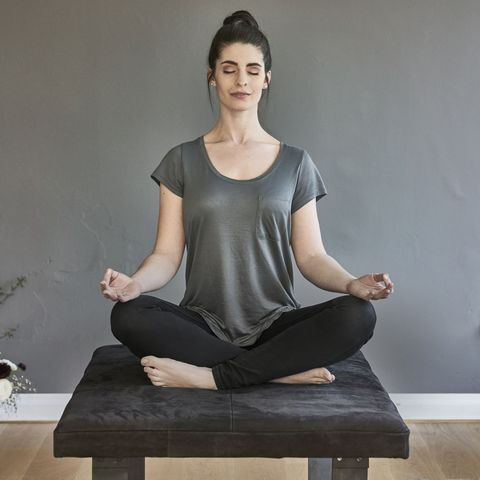 young woman sitting on lounge doing yoga