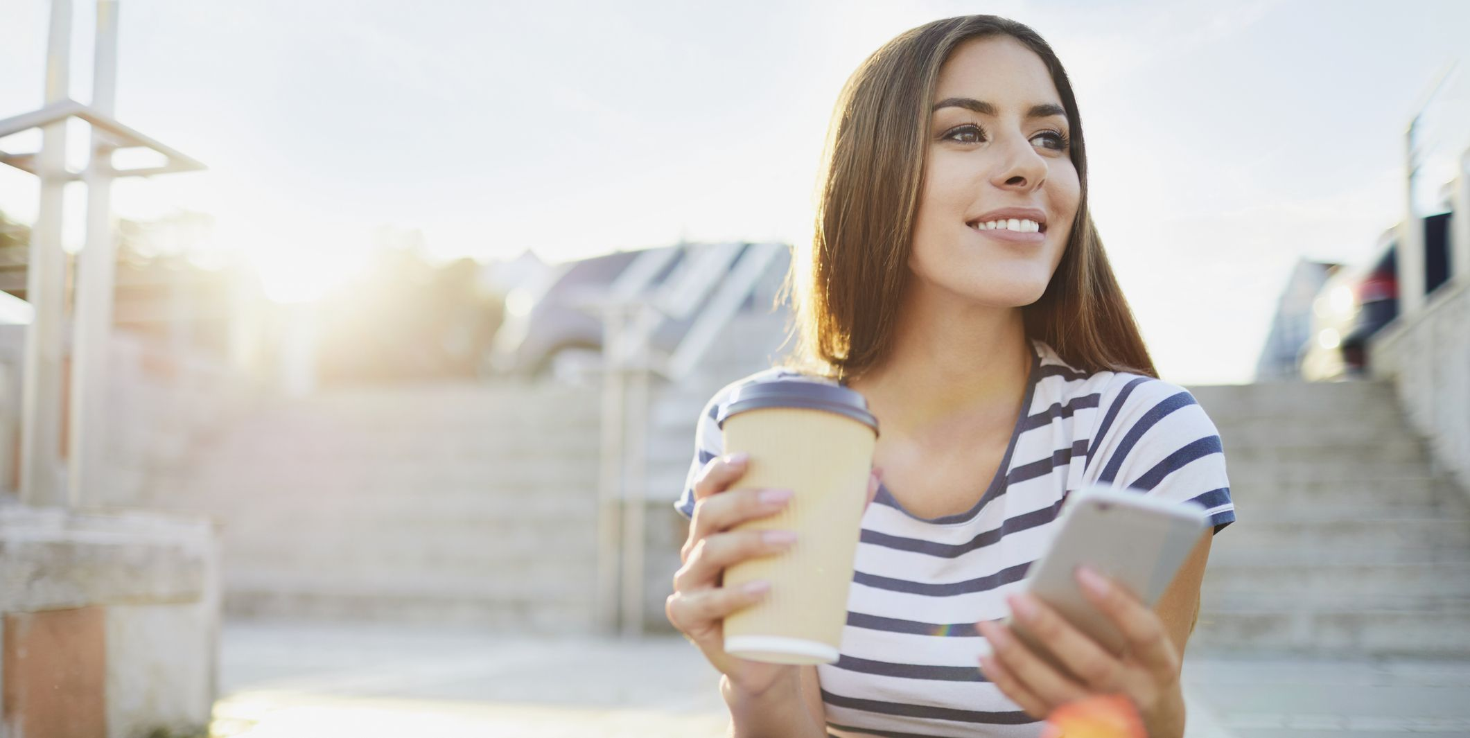 Young woman sitting on stairs in the city with phone and coffee