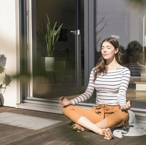 Young woman sitting on terrace at home practicing yoga