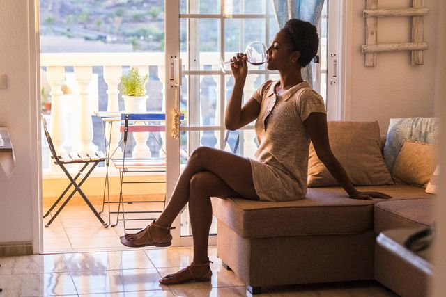 young woman sitting on the couch drinking glass of red wine