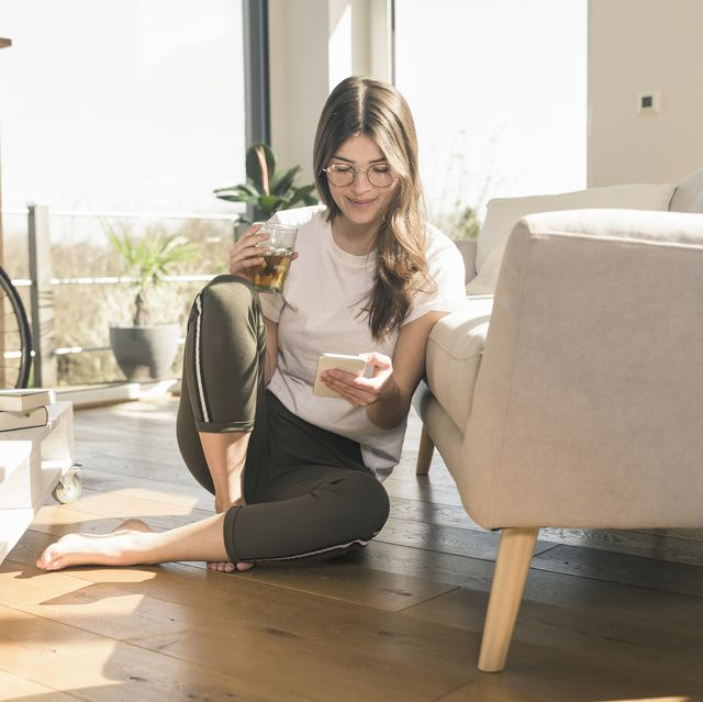 young woman sitting on the floor at home with drink and cell phone