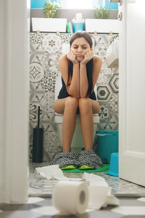 young woman sitting on the toilet seat unable to fetch toilet paper