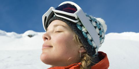 A young woman soaks in the sun while skiing the backcountry of the Selkirk Mountains, Canada.