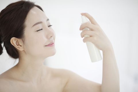 young woman spraying mist on face with eyes closed