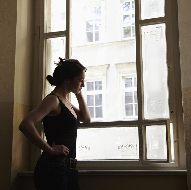 young woman standing in a stairway looking outside the window