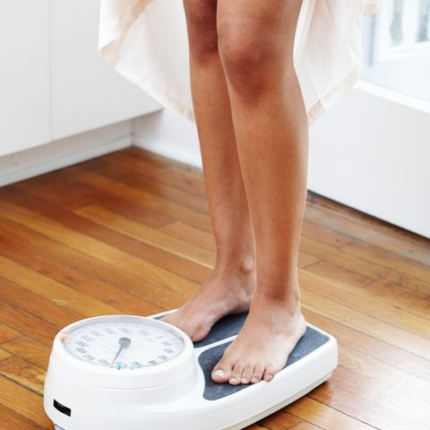 young woman standing on scales, low section