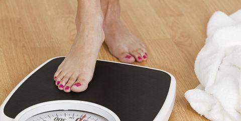 Young woman stepping on a weighing scale