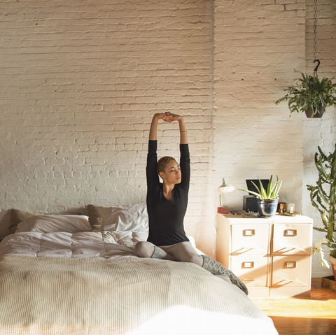 Young woman stretching arms while sitting on bed at home