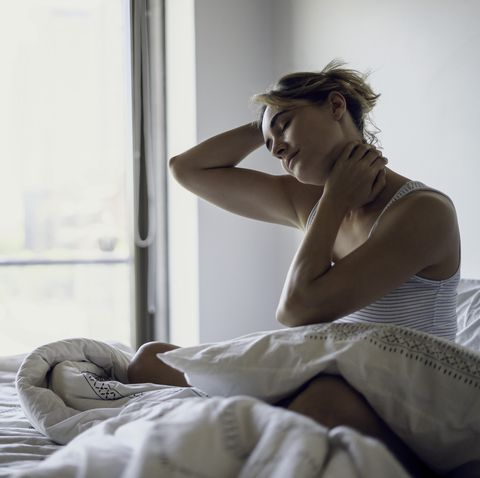 young woman stretching her neck on bed