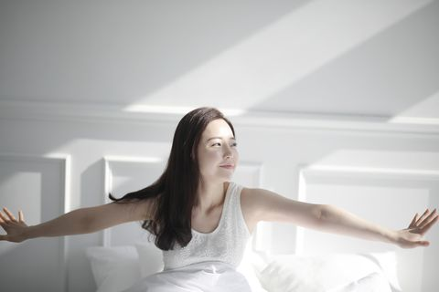 young woman stretching on bed