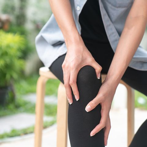 young woman suffering from pain in knee, close up